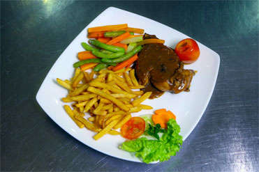 Delicious dish with French fries, boiled vegetables and steak
